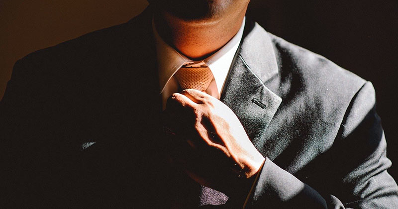 Confident man adjusting tie